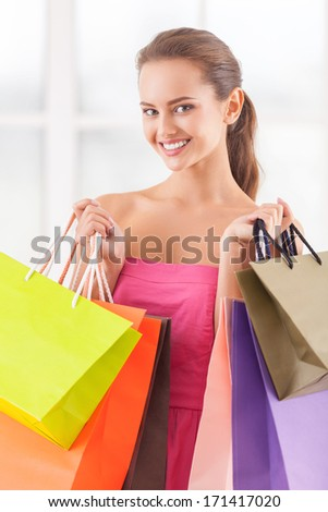 Good day for shopping. Beautiful young woman in pink dress holding shopping bags and smiling at camera