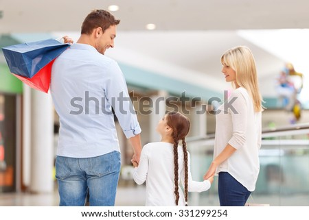 Good day. Pleasant friendly blissful family walking around the mall and making shopping while feeling happy - stock photo