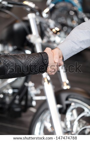 Good deal. Close-up of handshaking with a motorcycle on the background - stock photo