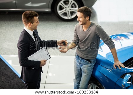 Good deal. High angle view of young car salesman making deal with customer at the dealership  - stock photo