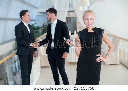 Good deal. Successful and motivated businesswoman is standing with mobile phone and smiling. Two her business partners are standing behind her on the background - stock photo