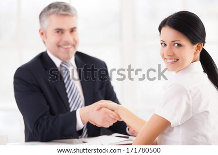 Good deal. Two people in formalwear handshaking and looking at camera while sitting at the table - stock photo
