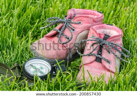 good direction - little baby booties in the grass with compass - stock photo