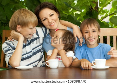 Good family sitting at a table on the veranda