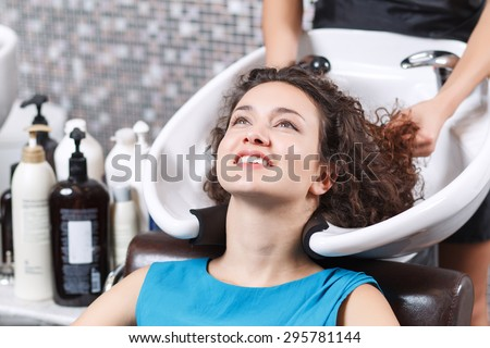 Good feeling. Close up of attractive young lady leaning her head backwards and smiling while having  hair washed in beauty salon