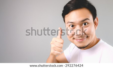 Good for you, face and thumb up sign. An asian man with white t-shirt and grey background. - stock photo