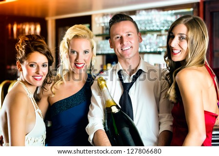 Good friends - bartender and women - with a large magnum bottle champagne at bar having fun - stock photo