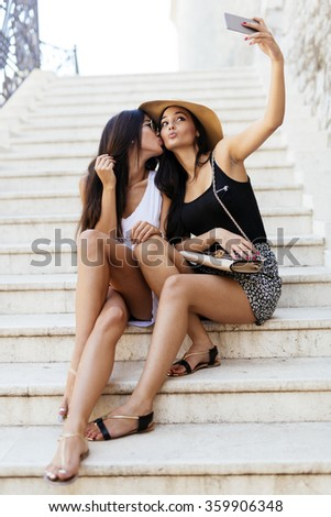 Good friends taking a selfie of themselves while sitting on stairs