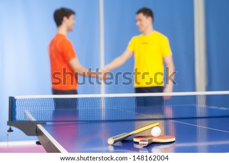 Good game! Two young men in sports clothing handshaking near the tennis table - stock photo