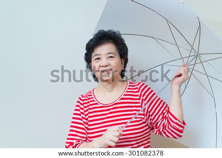 Good healthy asian woman smiling and holding white umbrella in studio shot, specialty tones with soft shadow
