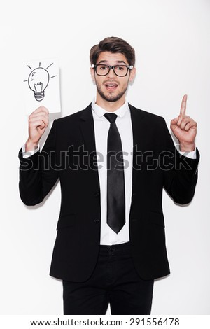Good idea! Excited young man in formalwear pointing up and holding picture of electric lamp while standing against white background - stock photo