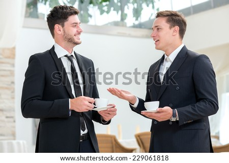 Good idea. Two successful and motivated businessmen are talking to each other while drinking coffee - stock photo