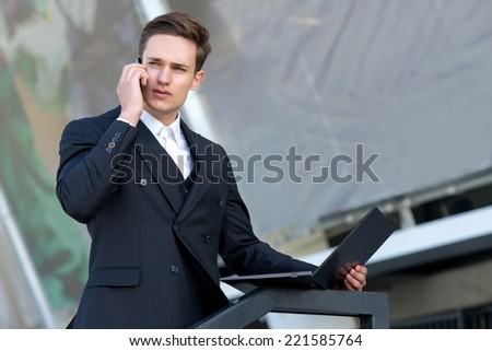 Good job on the mobile phone. Confident and motivated businessman is talking on a cell phone, while working with laptop - stock photo