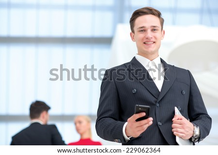 Good job. Young and motivated businessman is standing with mobile phone and tablet. Businessman is open-minded and smiling honestly - stock photo