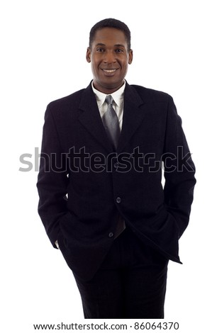 Good looking African American business man standing with hands in pockets isolated white background - stock photo