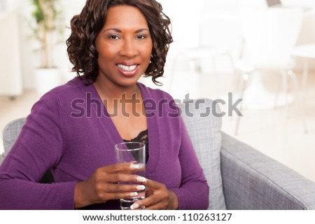 Good looking African American lady relaxing at home wearing purple sweater.
