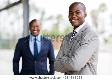 good looking afro american business man with colleague on background