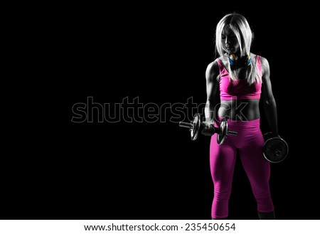 Good looking athletic woman pumping up muscles with dumbbells - stock photo