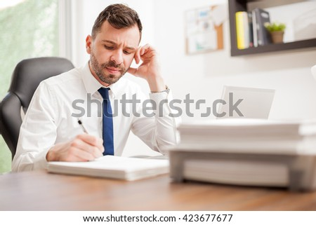 Good looking attorney overwhelmed at work, signing a pile of documents looking angry and tired