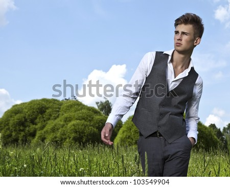 Good looking beautiful young man on the field. - stock photo
