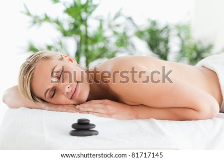 Good looking blonde woman lying on a lounger with eyes closed in a wellness center - stock photo