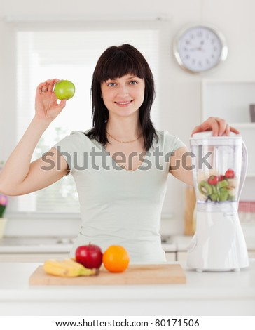 Good looking brunette female posing while standing in the kitchen