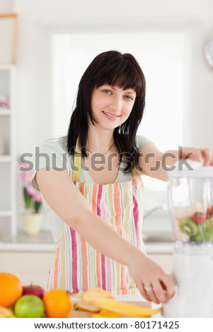 Good looking brunette woman using a mixer while standing in the kitchen