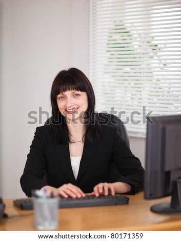 Good looking brunette woman working on a computer while sitting at a desk in the office