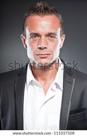 Good looking business man blue eyes and short blond hair. Tough guy. Wearing white shirt and black jacket. - stock photo