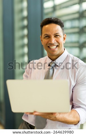 good looking corporate worker holding laptop - stock photo