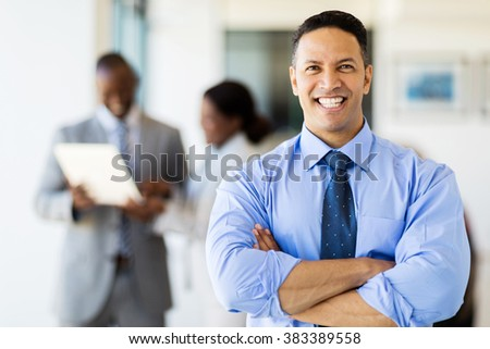good looking corporate worker in modern office with colleagues on background - stock photo