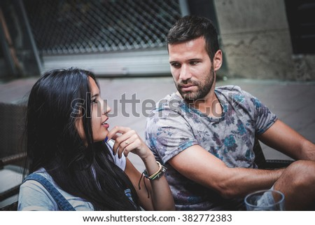 Good looking couple talking in a bar