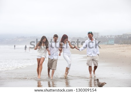 Good looking family with teens walking and talking on the beach at Santa Monica Ca