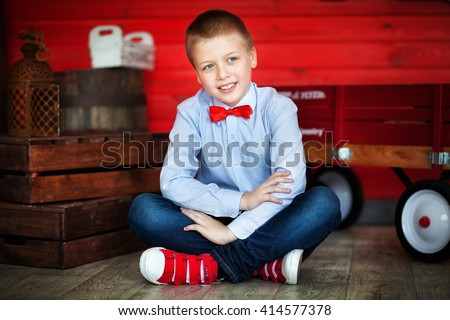 Good looking fashion child in red shoes and red bow-tie.Happy smiling teenager boy with blue eyes sitting on a floor indoor. Red wood background. - stock photo
