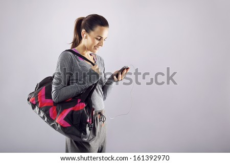 Good looking female athlete with a sports bag listening to music on her mobile phone. Fitness woman in sports clothing going to gym on grey background - stock photo