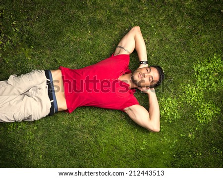 Good looking, fit male model relaxing lying on the grass, looking at camera, photographed right from above