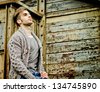 Good looking guy leaning against rusty metal and wooden walls - stock photo