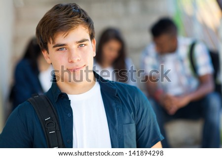 good looking highschool boy with friends on background - stock photo