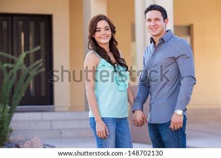 Good looking Hispanic newlyweds arriving to their new house and holding hands - stock photo
