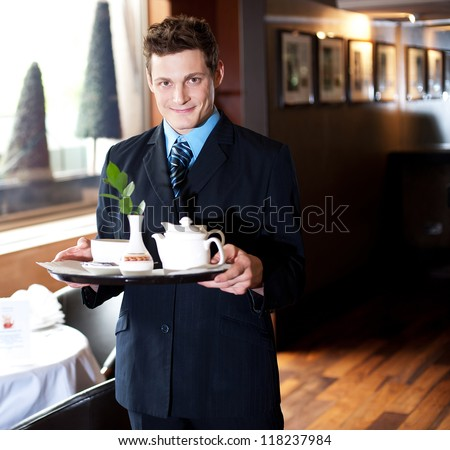 Good looking host in a restaurant holding tea tray for guests - stock photo