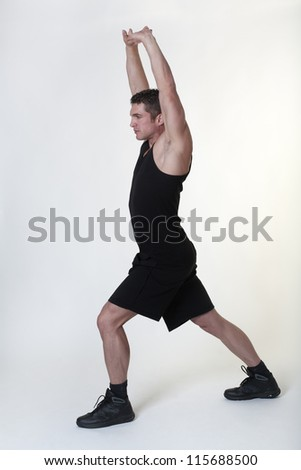good looking male bodybuilder doing some stretching exercises before his does his daily workout - stock photo