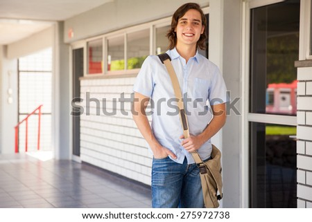 Good looking male college student with a school bag standing in a hallway and smiling - stock photo