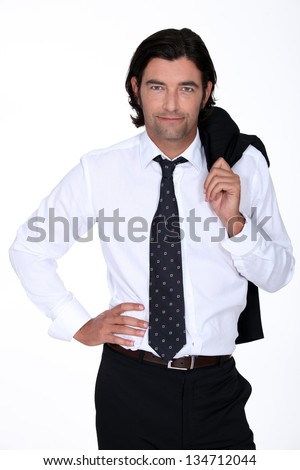 Good looking man in a suit holding his jacket over his shoulder - stock photo