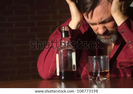 Good-looking man sits quietly at his home at the table - stock photo