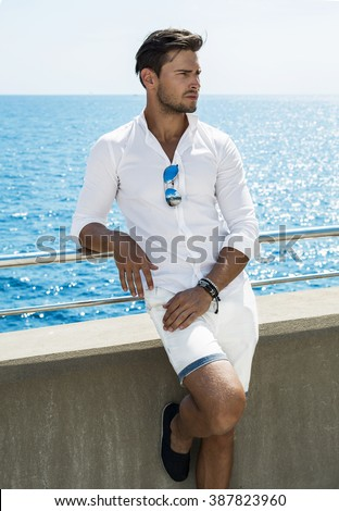 Good looking man wearing white clothes by the sea - stock photo