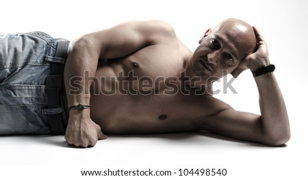 Good looking man with his shirt of lying on the floor - stock photo