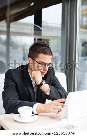 Good-looking manager sitting at desk, using tablet in cafe - stock photo