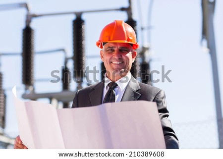 good looking middle aged electrical manager with blueprint