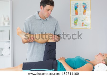 Good looking physiotherapist controlling knee of a patient in bright office - stock photo