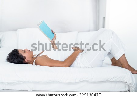 Good looking pregnant woman reading a book while lying on a bed at home